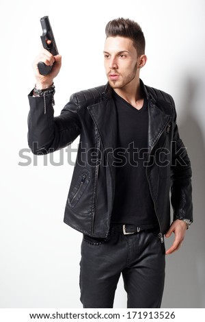 Portrait Of A Man Holding Gun against a white background not isolated.Fashion photo. - stock photo