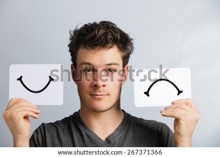 Portrait of a Man Holding Happy and Unhappy Survey Mood Board - stock photo