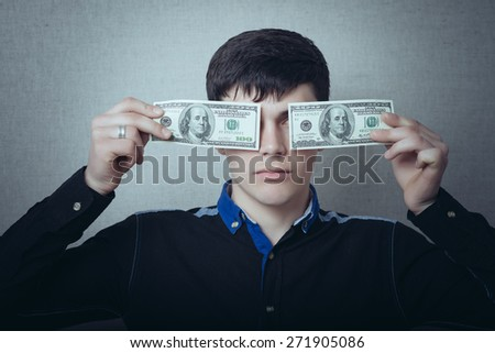 Portrait of a man holding money over gray background - stock photo