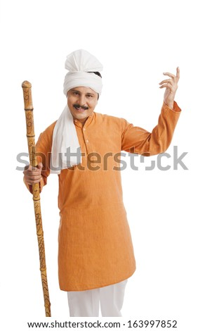 Portrait of a man holding wooden staff and gesturing - stock photo
