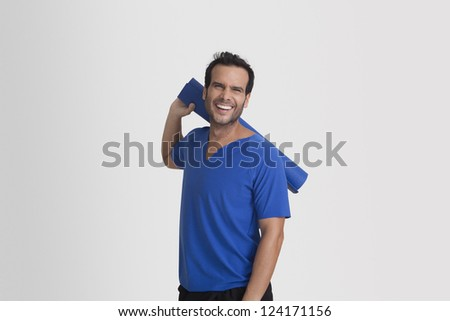 Portrait of a man holding yoga mat and smiling - stock photo