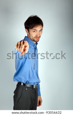 portrait of a man in a blue shirt pointing a finger in front of - stock photo