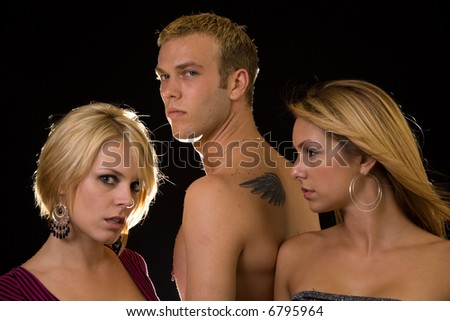 Portrait of a man in between two woman, one woman looking at the other to show jealousy