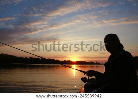 Portrait of a man in profile in a boat on a river with a fishing pole in his hands at sunset in autumn