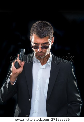 Portrait of a man in suit with handgun - stock photo