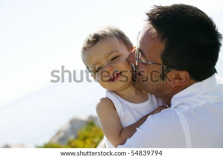 Portrait of a man kissing a little boy on the cheek