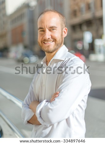 Portrait of a man leaning on a rail in the street
