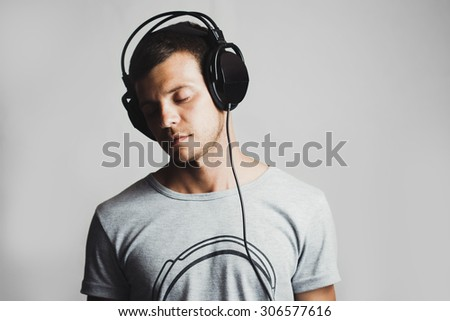 Portrait of a man listening to music on headphones, gray background  - stock photo