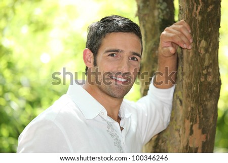 portrait of a man next to a tree - stock photo