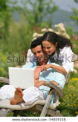 Portrait of a man on a deck chair and a woman in front of a laptop computer - stock photo