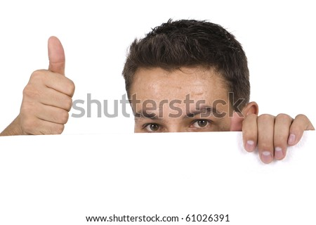Portrait of a man peeking behind empty white billboard and making ok sign