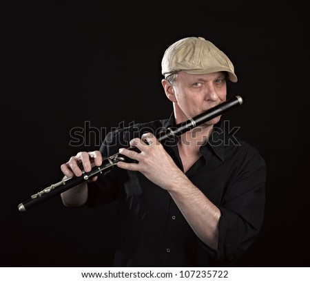 Portrait of a man playing old wooden transverse flute, isolated on black - stock photo