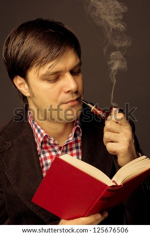 Portrait of a man reading and smoking a pipe isolated on grey background - stock photo