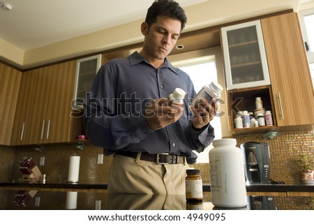 Portrait of a man reading pill bottles - stock photo