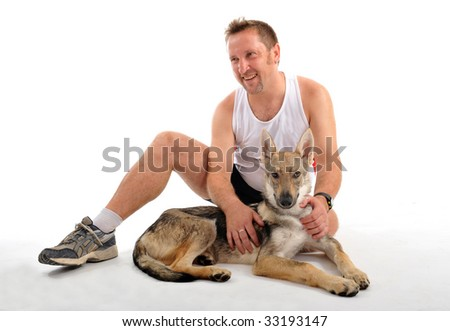 portrait of a man resting after sport training with his puppy - stock photo