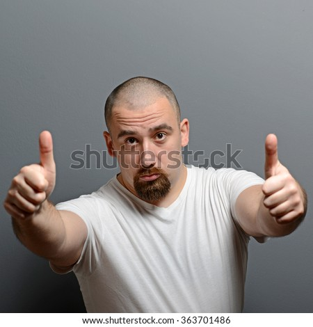 Portrait of a man showing thumb up or ok sign against gray background - stock photo
