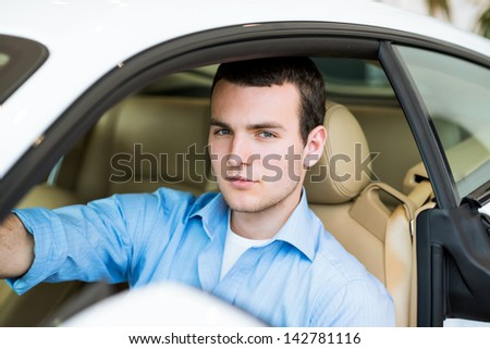 portrait of a man sitting in a sports car in the showroom, make expensive purchases