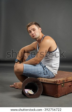 Portrait of a man sitting on a retro suitcase and begging with hat - stock photo