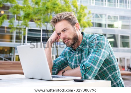 Portrait of a man sitting outside in the city with laptop - stock photo