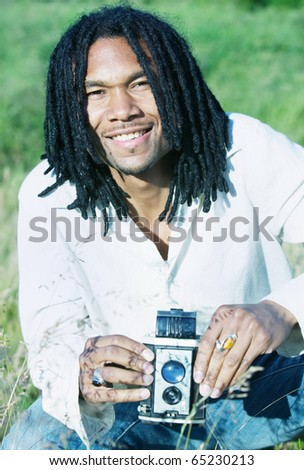 Portrait of a man smiling holding an old camera
