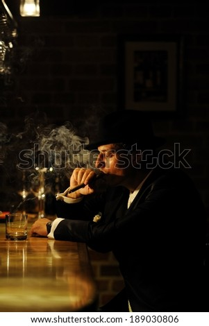 Portrait of a man smoking cigar by the bar. Mafia, retro or gangster style.
