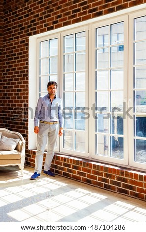 Portrait of a man standing at the window and looking at the camera