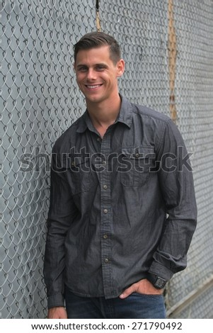 Portrait of a man standing in front of a chain link fence.   - stock photo