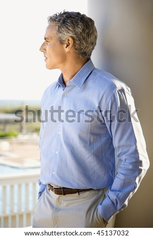 Portrait of a man standing on porch with his back to a column looking out towards the coast. - stock photo