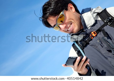 portrait of a man texting outdoors and smiling - stock photo