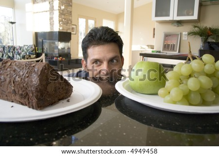 Portrait of a man trying to decide whether to cake or grapes - stock photo