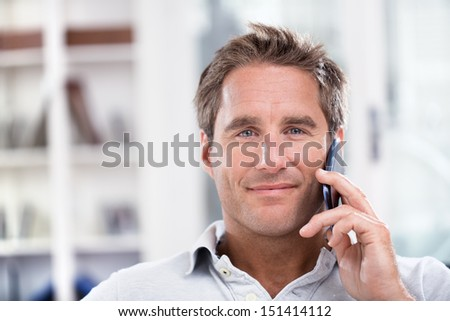 Portrait of a man using cell phone while sitting on sofa at home, smiling at camera. - stock photo