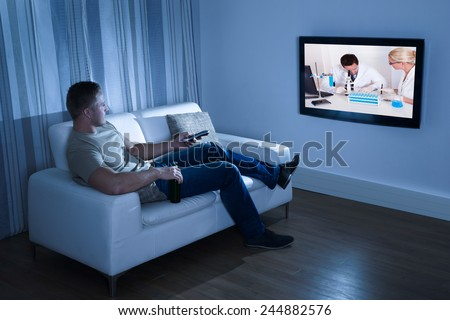 Portrait Of A Man Watching Television Sitting On Couch - stock photo