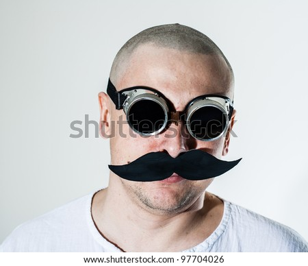 Portrait of a man wearing false moustache and black welding goggles - stock photo