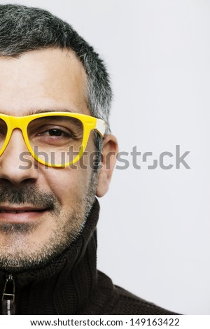 Portrait of a man wearing yellow glasses and smiles. Studio shot. Grain added. - stock photo
