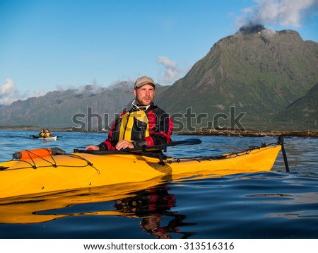 Portrait of a man with a beard sitting in a kayak on the background of a large mountain and blue sky with clouds
