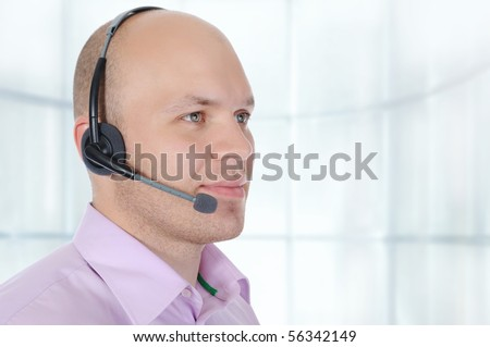 Portrait of a man with a headset in a bright office - stock photo