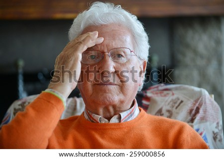 Portrait of a man with headache in his house - stock photo