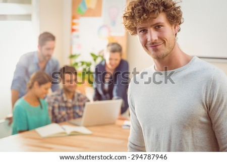 Portrait of a man with his colleague behind him in the office - stock photo