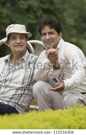 Portrait of a man with his father in a park