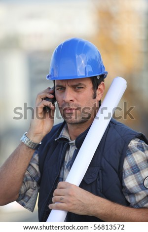 Portrait of a man with safety helmet and a mobile phone - stock photo