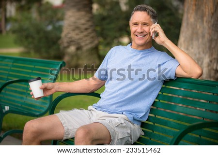 Portrait of a man with salt and pepper hair using his cell - stock photo