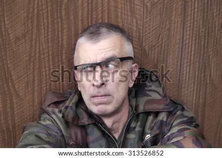 Portrait of a man with suspicious gaze, wearing military style jacket and sitting next to wooden wall - stock photo