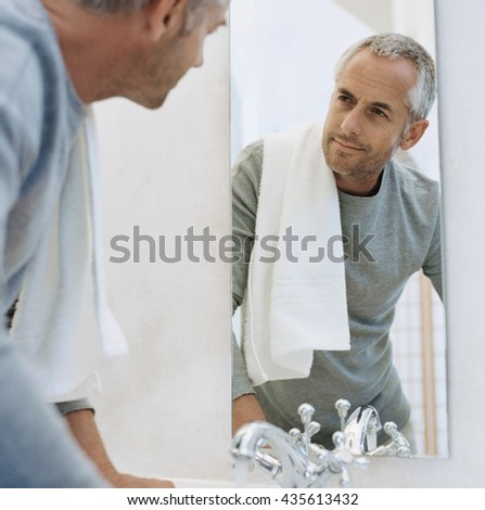 Portrait of a man with towel looking at his reflection in the mirror in bathroom - stock photo