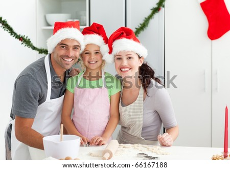 Portrait of a man with wife and daughter cooking Christmas biscuits in the kitchen - stock photo