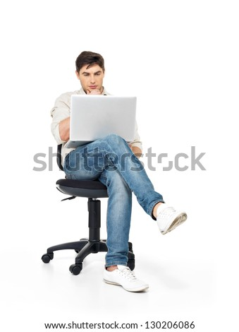 Portrait of a man working on laptop sitting on the chair - isolated on white. - stock photo