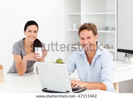 Portrait of a  man working on the laptop while his girlfriend is drinking coffee in the kitchen - stock photo