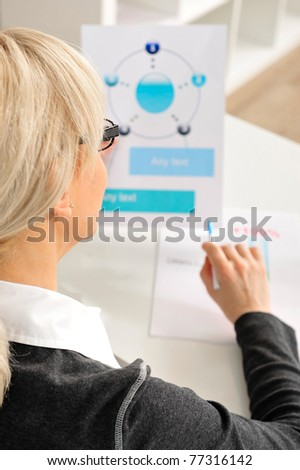 Portrait of a mature attractive business woman looking on her statistics