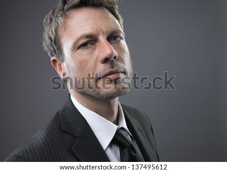 Portrait of a mature business man against grey background - stock photo