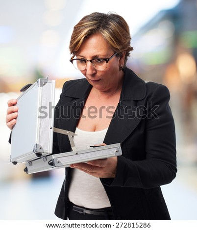 portrait of a mature business woman looking into a suitcase - stock photo