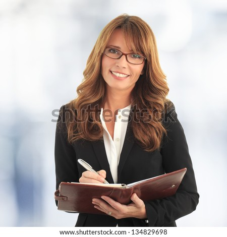 Portrait of a mature business woman writing in her notebook
